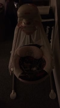 baby's white and peach cradle swing