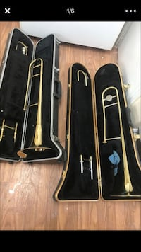 two brass-colored wind instruments with cases