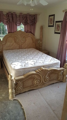 Brown wooden carved bed frame with white quilted m in for Quilted bed frame