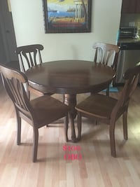 Round brown wooden table with four chairs dining set. Top has some wear. Base and chairs do not. Solid wood.  Longwood, 32779
