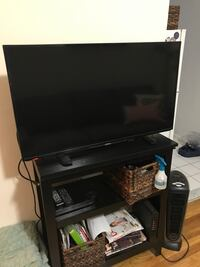 black flat screen TV with black wooden TV stand New York, 10010