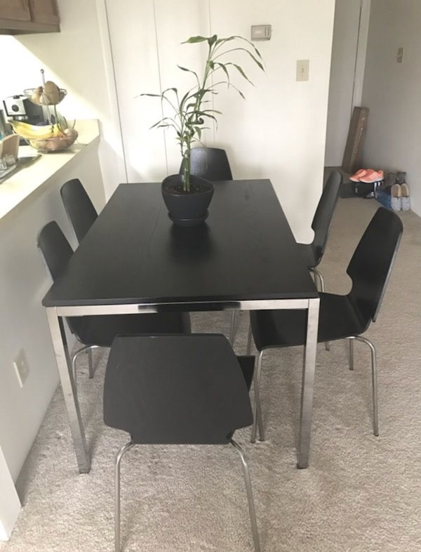 Rectangular black wooden table with six chairs dining set. Price as marked.