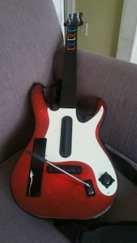 Black, red, and white guitar hero controller
