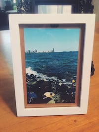 sea and rocks photo with white wooden frame