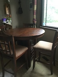 round brown wooden table with four chairs dining set Kelowna, V1Y 1T1