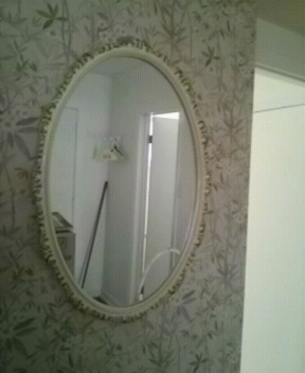 oval white and gray framed wall mirror