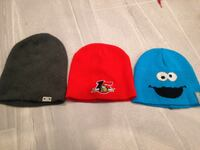 Three red, grey, and blue knit caps