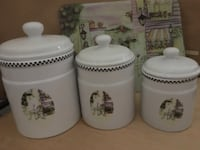 three white ceramic canisters and matching cutting board