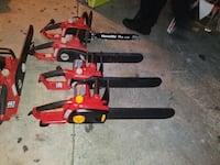 four red-and-black chainsaws