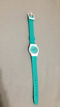 round teal analog watch with teal strap