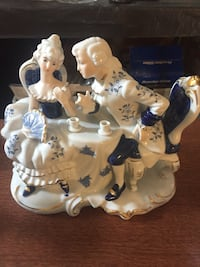 man and woman ceramic figurine stand