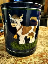 blue pottery utensil holder with a cow painted on it