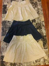 Three navy blue and tan pleated skirts .