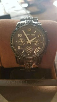 round black chronograph watch with silver link bracelet Calgary, T2Z 2K4