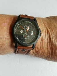 1 black watch with brown watchband.