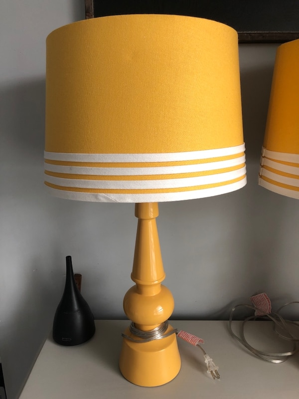 Two tall yellow table lamps.  4f864463-f12d-45c8-b50d-f12a3eea8d6e