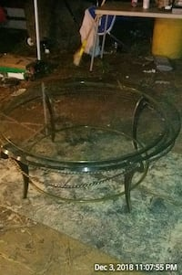 round clear glass-top table with black steel base 306 mi