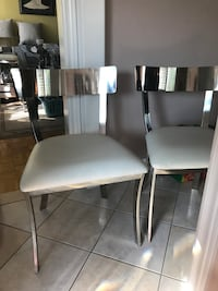 $300 for a set of 2 New Metal Kitchen Chairs with white leather seats and a set of 2 of breakfast/bar chairs. (Also available 4 Breakfast chairs) My friend used it only for home staging, she paid $250 ea. plus tax. In smoke free and pet free home pickup K Brampton, L6Z