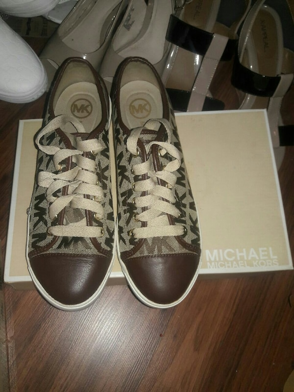 pair of brown-and-gray Michael Kors low-top sneakers