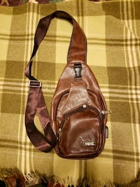leather like shiny brown sling pack, w charge opening. back back. new