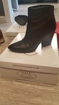 Unpaired black leather boots on box
