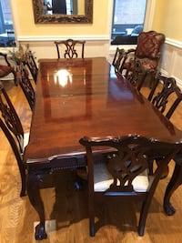 Rectangular brown wooden table with ten chairs dining set. Two removable leaves. Solid wood furniture. Chairs have light cover and some are stained. Nashville, 37220
