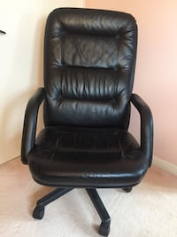 Black leather padded rolling armchair