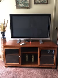Gray flat screen tv with brown wooden tv hutch not negotiable