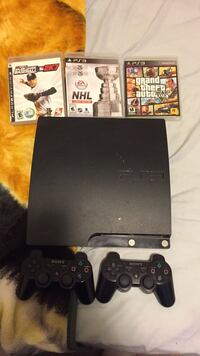 black Sony PS3 slim console with controller and game cases
