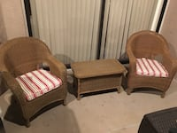 pair of brown wicker armchairs and side table