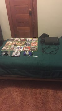 Black Xbox 360 console with controller and games