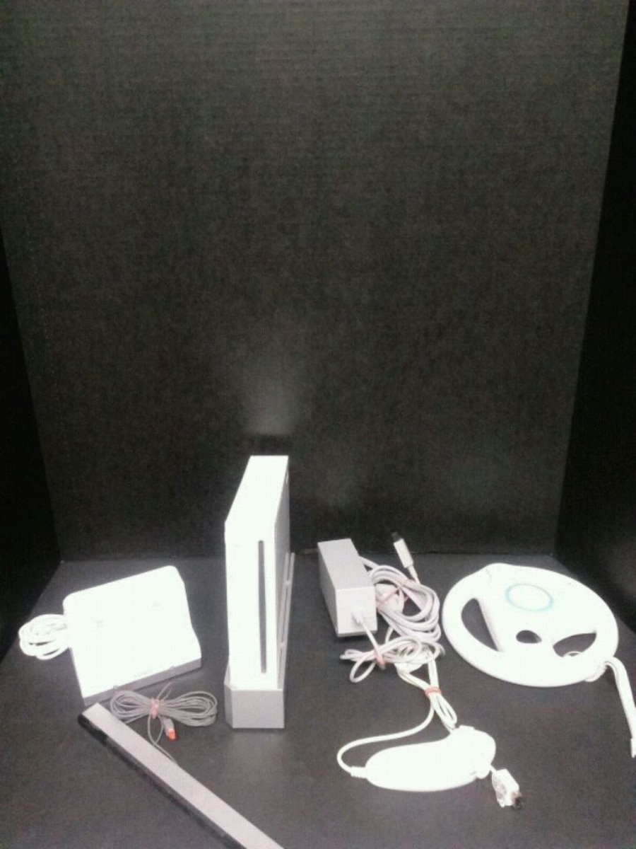 Photo Wii console w/sensor bar, numchuck, steering wheel, charging station.