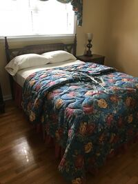 multicolored floral bedspread and brown wooden bed