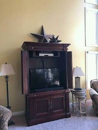 flat screen television with brown wooden TV hutch Greenfield, 46140
