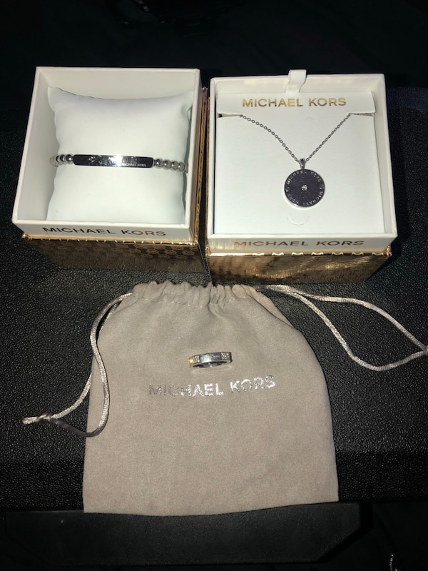 silver-colored Michael Kors pendant, necklace, and ring set