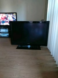 black flat screen TV with brown wooden TV stand 3125 km