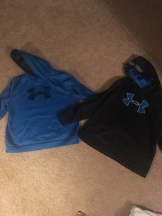 two blue and black Under Armour pull over hoodies