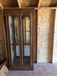 Brown wood and glass curio cabinet