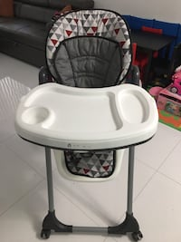 gray, white, and red tribal high chair with feeding tray
