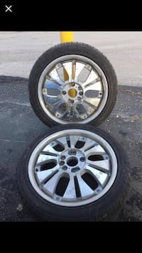 4 gray multi-spoke vehicle wheel with tires