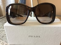 black framed Prada over-sized sunglasses on box