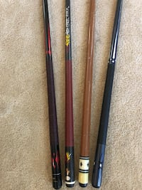 two black and brown cue sticks