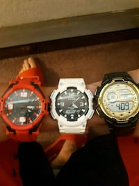 three assorted-color digital watches
