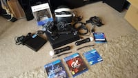 black Sony PS4 console with controllers and game cases