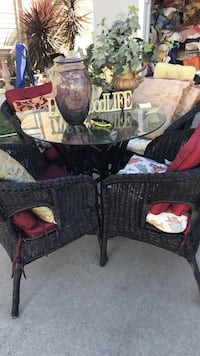 Black wicker set with 4 chairs and glass table / pillows included