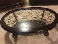 Oval clear glass top center table with brown wooden frame