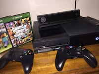 Black xbox one console with controllers and game cases