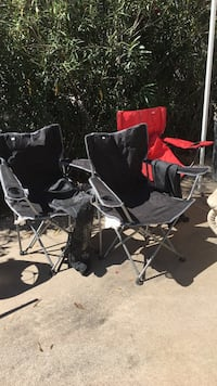 two black and one red fabric camping chairs