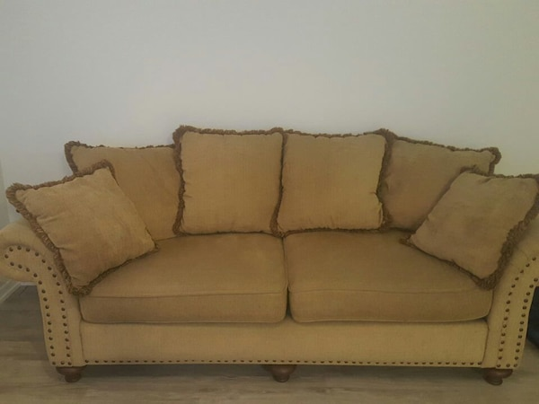 beige fabric 2-seat sofa and throw pillow