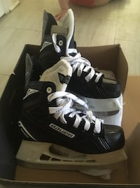 pair of black-and-white Bauer ice skates with box